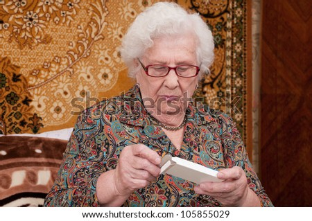 Senior woman reads prescriptions and takes out pills