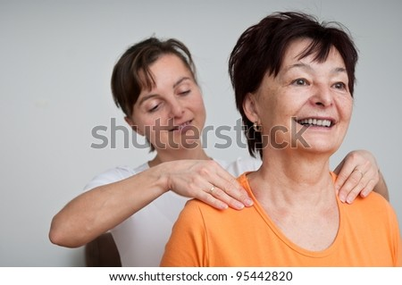 Senior woman receives neck massage from young person