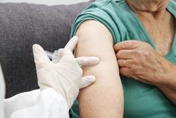 Senior woman receiving vaccine. Medical worker vaccinating an elderly patient against flu, influenza, pneumonia or coronavirus.