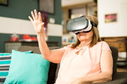 Senior woman relaxing at home and having fun with her VR glasses