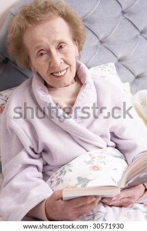 Senior Woman Relaxing In Bed With Book - stock photo