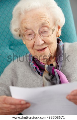 Senior Woman Relaxing In Chair Reading Letter