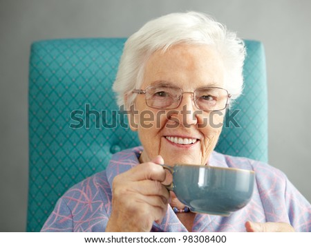 Senior Woman Relaxing In Chair With Hot Drink