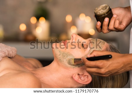 Senior woman relaxing while beautician getting purifying clay mask on her face. Closeup hand of masseuse applying mud on face of mature lady in spa center. Anti aging facial treatment with brush.