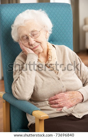 Senior Woman Resting In Chair At Home - stock photo