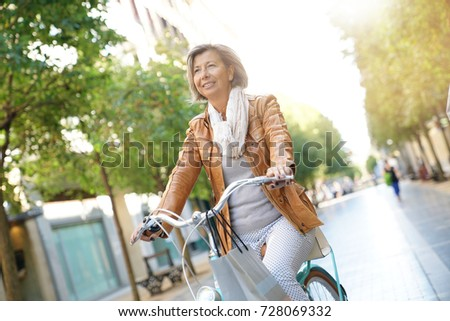Senior woman riding city bike in town