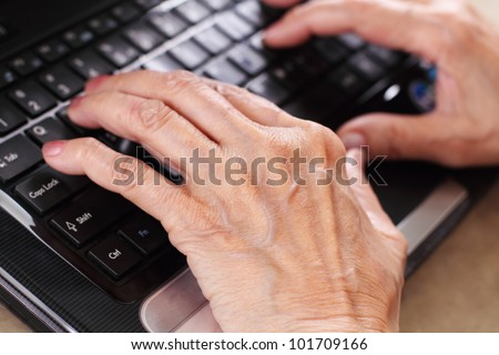 Senior woman's hand in the computer.Close up.