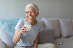 Senior woman's hands holding a glass of milk. Happy senior woman having fun while drinking milk at home. Senior Woman drinking a glass of milk to maintain her wellbeing.