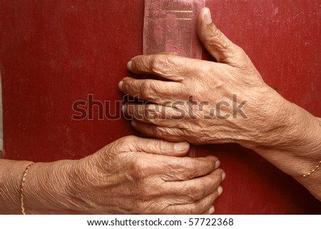 Senior woman's hands holding an old book