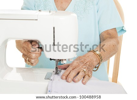 Senior woman's hands using her sewing machine. White Background.