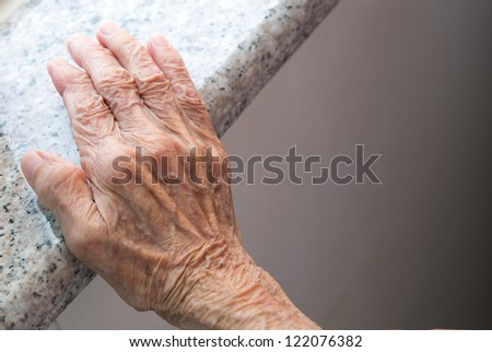 Senior woman's wrinkled hand near the window.