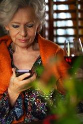 Senior woman sending a voice message. Mature woman recording a voicemail on a mobile phone.