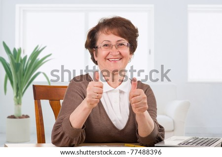 Senior woman showing thumbs up sitting on desk at home