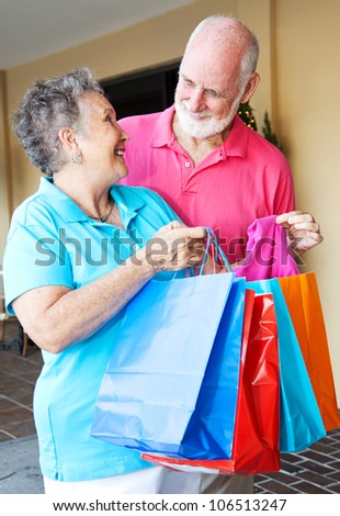 Senior woman shows her husband some of the bargains she got shopping.
