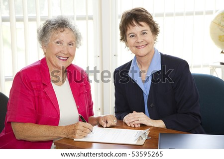 Senior woman signs paperwork in mature businesswoman's office. - stock photo