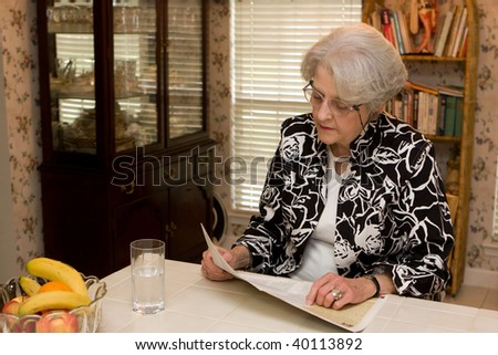 Senior woman sits at counter in the kitchen with glass of water and reads magazine at home.