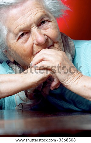 Senior woman sits at the table and looks at the camera - stock photo
