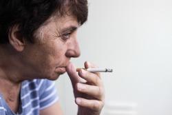 Senior woman sitting and smoke a cigarette