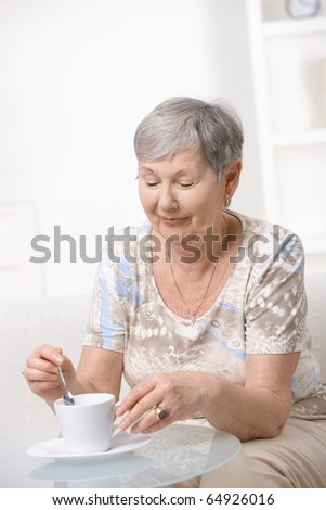 Senior woman sitting at coffee table, drinking coffee.? - stock photo