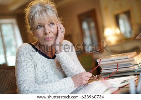 Senior woman sitting at desk and writing on book
