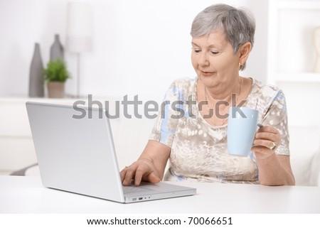 Senior woman sitting at desk using laptop computer, looking at screen.?