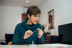 Senior woman sitting at home, studying the instructions for a self test for COVID-19 with Antigen kit on hand. Holds a nasal swab for possible infection of Coronavirus. Health services online.