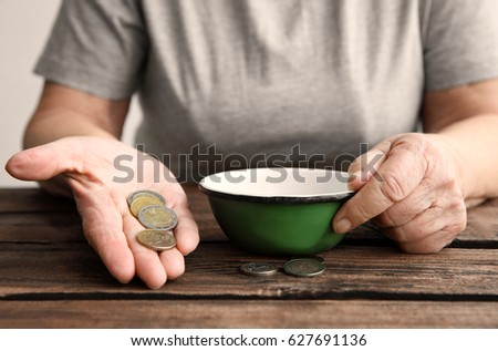 Senior woman sitting at table with bowl and coins, closeup. Poverty concept #627691136