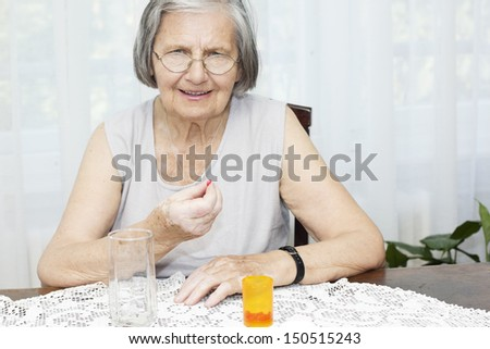 Senior woman sitting at the desk looking at camera and holding a pill.