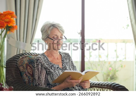Senior woman sitting in chair and reading a book #266092892