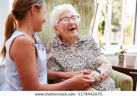 Senior Woman Sitting In Chair And Talking With Nurse In Retirement Home