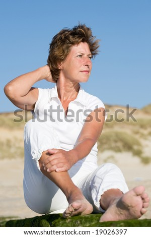 Senior woman sitting on a stone at the beach. Sunset time