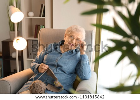 Senior woman sitting on armchair while knitting sweater at home #1131815642