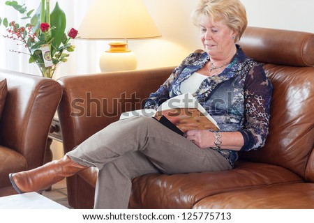 Senior woman sitting on brown leather couch in living room reading a book
