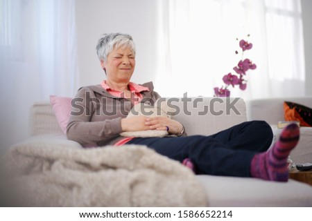 Senior woman sitting on couch in pain