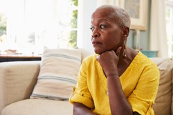 Senior Woman Sitting On Sofa At Home Suffering From Depression