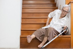 Senior woman sitting on the floor of the staircase with pain in hips and back,tripped or lose balance as she walked downstairs causing accidents,old elderly slipped and fell was injured by dizziness