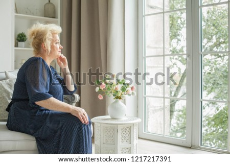 Senior woman sitting on the sofa and looking at the window at home #1217217391