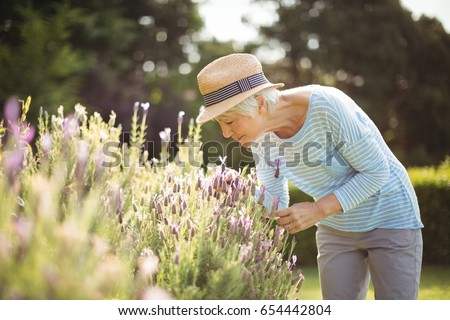 Senior woman smelling flowers in garden