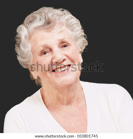 senior woman smiling against a black background