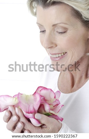 Senior woman smiling and holding flower petals in hands