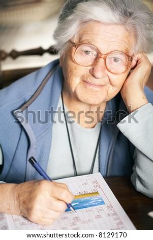 Senior woman solving crossword puzzle, portrait