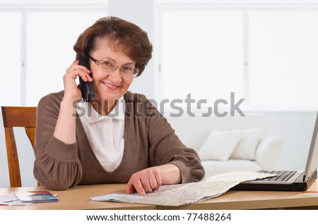 senior woman speaking on phone choosing vacations