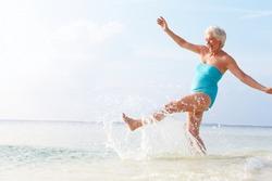 Senior Woman Splashing In Sea On Beach Holiday
