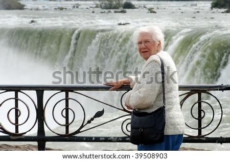 senior woman standing at niagara falls