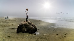 Senior Woman standing on a large Driftwood Log looking out into the Dense Fog over the Pacific Ocean in Cox Bay at the Pacific Rim National Park on Vancouver Island, British Columbia, Canada