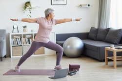 Senior woman standing on exercise mat exercising during sports training in the living room at home