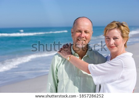 Senior woman standing on the beach with her arms around her husband on a bright, sunny day Stock photo ©