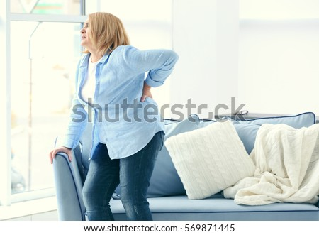 Senior woman suffering from backache at home #569871445