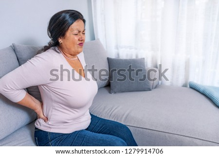 Senior woman suffering from backache at home. Mature woman suffering from backache at home. Massaging lower back with hand, feeling exhausted, in living room