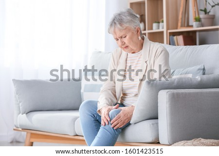 Senior woman suffering from pain in knee at home